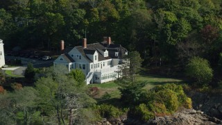 AX147_055 - 6k stock footage aerial video approaching an oceanfront mansion among trees, autumn, Beverly, Massachusetts