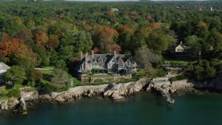 AX147_061 - 6k stock footage aerial video orbiting oceanfront mansion among fall foliage, autumn, Manchester-by-the-Sea, Massachusetts