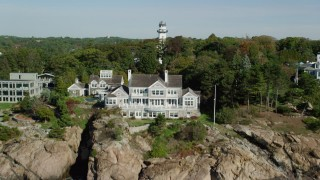 AX147_064 - 6k stock footage aerial video revealing oceanfront homes and lighthouse among trees, Manchester-by-the-Sea, Massachusetts
