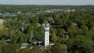 AX147_065 - 6k stock footage aerial video flying over a light house and coastal community among trees, Manchester-by-the-Sea, Massachusetts