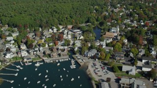 AX147_068 - 6k stock footage aerial video flying over harbor and coastal community toward trees, autumn, Manchester-by-the-Sea, Massachusetts