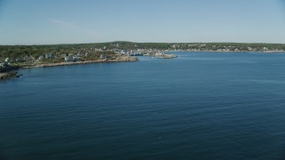 AX147_117 - 6k stock footage aerial video flying over water, small coastal town in distance, Rockport, Massachusetts
