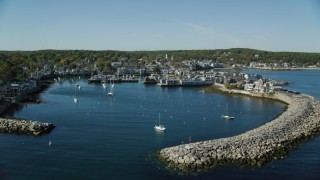 AX147_118 - 6k stock footage aerial video flying over harbor toward coastal town, Rockport, Massachusetts