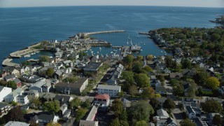 AX147_122 - 6k stock footage aerial video flying by small coastal town and white church toward harbor, Rockport, Massachusetts