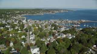 AX147_123 - 6k stock footage aerial video flying along small coastal town with church in the distance, Rockport, Massachusetts