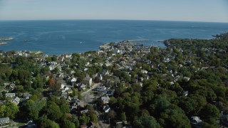 AX147_126 - 6k stock footage aerial video orbiting a small coastal town among trees, Rockport, Massachusetts