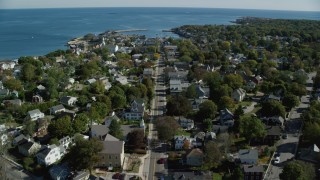 AX147_127 - 6k stock footage aerial video following a main street through a coastal town, Rockport, Massachusetts