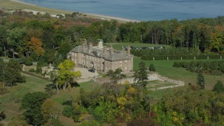 AX147_141 - 6k stock footage aerial video of The Great House at Crane Estate and Castle Hill among trees in autumn, Ipswich, Massachusetts