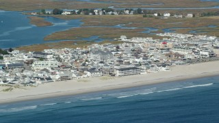 AX147_154 - 6k stock footage aerial video flying by a coastal town and beach, Hampton, New Hampshire