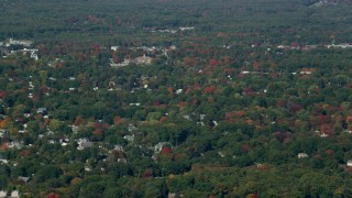 AX147_157 - 6k stock footage aerial video flying over houses among colorful autumn trees, Hampton, New Hampshire