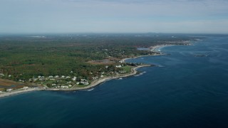 AX147_159 - 6k stock footage aerial video following the coastline and autumn trees, Hampton, New Hampshire
