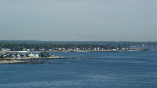 AX147_163 - 6k stock footage aerial video tracking a flock of birds above a coastal town, autumn, Rye, New Hampshire