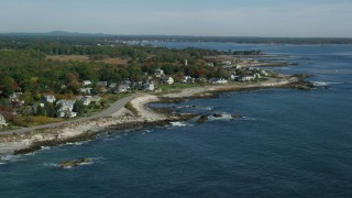 AX147_167 - 6k stock footage aerial video flying over ocean toward beachfront homes in autumn, Rye, New Hampshire