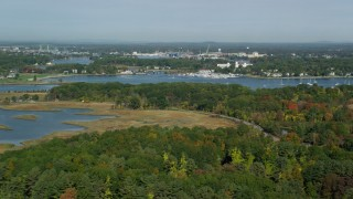 AX147_169 - 6k stock footage aerial video flying over marshland and forest toward harbor in autumn, Rye, New Castle, New Hampshire