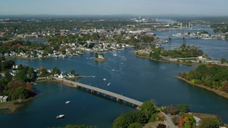 AX147_173 - 6k stock footage aerial video flying over a small bridge toward a coastal town in autumn, Portsmouth, New Hampshire