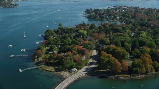 AX147_189 - 6k stock footage aerial video of a small bridge approaching coastal homes in autumn, New Castle, New Hampshire