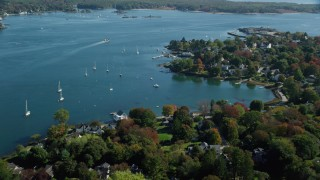 AX147_190 - 6k stock footage aerial video approaching a coastal community in autumn, New Castle, New Hampshire