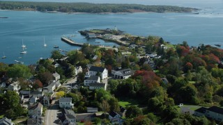 AX147_191 - 6k stock footage aerial video flying over coastal community in autumn toward a lighthouse, New Castle, New Hampshire