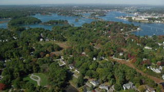 AX147_199 - 6k stock footage aerial video flying over autumn trees in a coastal town, New Castle, Portsmouth, New Hampshire