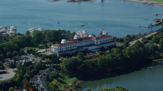 AX147_200 - 6k stock footage aerial video orbiting Wentworth by the Sea hotel in autumn, New Castle, New Hampshire