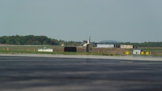 AX147_212 - 6k stock footage aerial video tracking a military plane landing, Portsmouth International Airport, New Hampshire