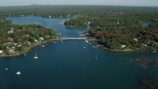AX147_225 - 6k stock footage aerial video flying by small bridge, waterfront communities, autumn, Kittery, Maine