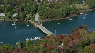 AX147_226 - 6k stock footage aerial video flying by small bridge, colorful trees, Kittery, Maine