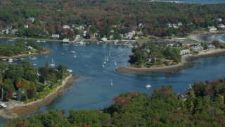 AX147_231 - 6k stock footage aerial video approaching coastal town, tilt up to colorful forest, autumn, York, Maine