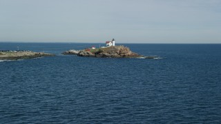 AX147_236 - 6K stock footage aerial video flying low over the ocean, approaching Cape Neddick Light, York, Maine