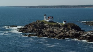 AX147_238 - 6k stock footage aerial video orbiting Cape Neddick Light, coastal town in autumn, York, Maine
