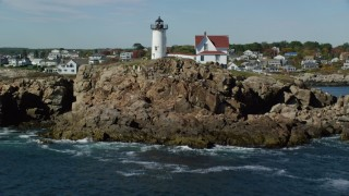 AX147_241 - 6k stock footage aerial video flying low over water, tilt up to reveal Cape Neddick Light, York, Maine