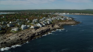 AX147_244 - 6k stock footage aerial video flying by coastal town, rocky shore, autumn, York, Maine