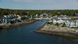 AX147_250 - 6k stock footage aerial video approaching oceanfront homes, small bridge, harbor, autumn, Ogunquit, Maine