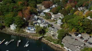AX147_251 - 6k stock footage aerial video flying over small bridge, small harbor, coastal town, autumn, Ogunquit, Maine