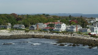 AX147_267 - 6k stock footage aerial video tilting up revealing oceanfront homes, Wood Island Light, Biddeford, Maine