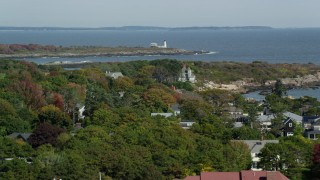 AX147_268 - 6k stock footage aerial video flying over coastal community, approach Wood Island Light, autumn, Biddeford, Maine