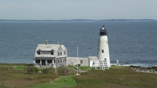 AX147_271 - 6k stock footage aerial video flying over Wood Island Light, approach Saco Bay, distant coastline, Biddeford, Maine