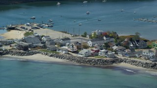 AX147_275 - 6k stock footage aerial video flying by oceanfront homes, boats in harbor, autumn, Saco, Maine
