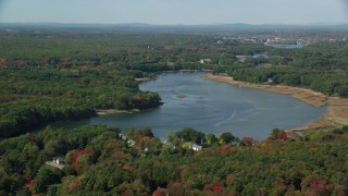 AX147_276 - 6k stock footage aerial video flying by the Saco River, colorful trees in autumn, Saco, Maine