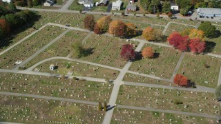 AX147_279 - 6k stock footage aerial video flying over dense, colorful forest, rural homes, approach cemetery, Biddeford, Maine