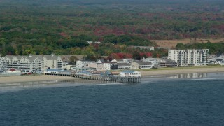 AX147_295 - 6k stock footage aerial video flying by beach and pier, colorful autumn trees, Old Orchard Beach, Maine