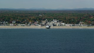 AX147_297 - 6k stock footage aerial video flying by beach, pier, Palace Playland, coastal town, autumn, Old Orchard Beach, Maine