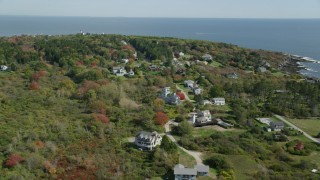 AX147_303 - 6k stock footage aerial video flying over upscale homes near ocean, autumn trees, Cape Elizabeth, Maine