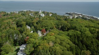 AX147_304 - 6k stock footage aerial video flying over coastal town, Cape Elizabeth Light, autumn, Cape Elizabeth, Maine
