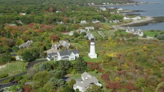 AX147_305 - 6k stock footage aerial video flying by coastal town, Cape Elizabeth Light, autumn, Cape Elizabeth, Maine