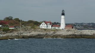 AX147_310 - 6k stock footage aerial video flying by Portland Head Light, autumn, Cape Elizabeth, Maine