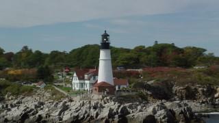 AX147_312 - 6k stock footage aerial video orbiting Portland Head Light, autumn, Cape Elizabeth, Maine