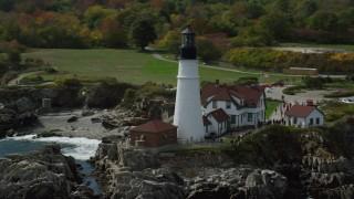 AX147_313 - 6k stock footage aerial video orbiting Portland Head Light, reveal coastline, autumn, Cape Elizabeth, Maine