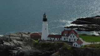 AX147_314 - 6k stock footage aerial video orbiting Portland Head Light, revealing rock formations, Cape Elizabeth, Maine