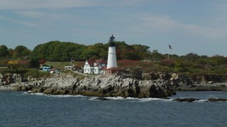 AX147_316 - 6k stock footage aerial video orbiting Portland Head Light, reveal colorful autumn trees, Cape Elizabeth, Maine